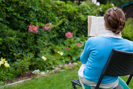 blessedness: Young woman reading a book in the garden