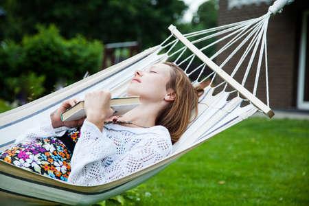relajado: Mujer que se relaja en hamaca en el jardín