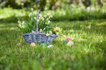 splint: Basket with flowers ann painted Easter eggs on the grass Foto de archivo