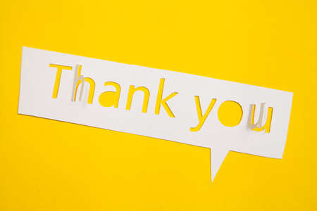 Speech bubble Thank you cut out from paper against yellow backdrop Stock Photo