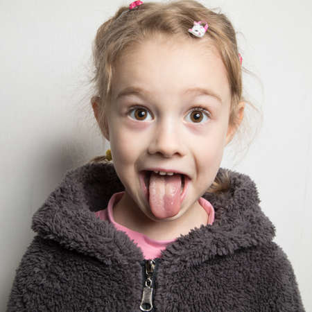 Happy little girl showing her tongue.