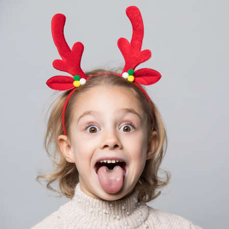 Cute young girl wearing deer horns. New year concept.
