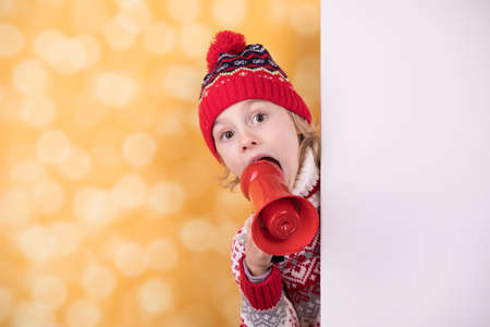 Little girl shouts something into the megaphone