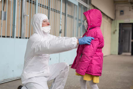 A man in a protective suit evacuates people