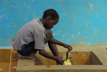 fills: mtito andeni- kenya july 2009. a child fills the bin of water  Editorial