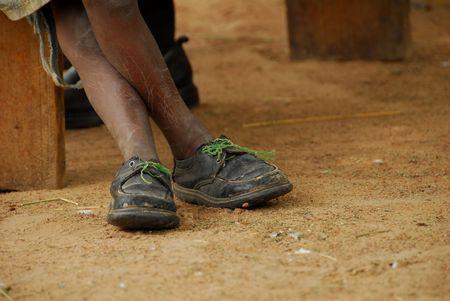 pobre niño con zapatos rotos  Foto de archivo