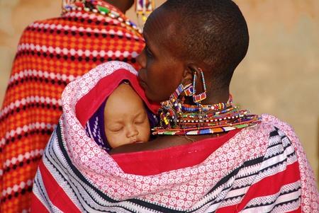 Masai Mara, Kenya - 13 de julio, madre de 2009:Masai con su hijo. La mujer lleva forjados de joyer�a tradicional de peque�as perlas de colores