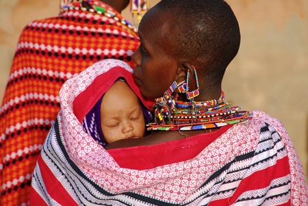 Masai Mara, Kenya - 13 de julio, madre de 2009:Masai con su hijo. La mujer lleva forjados de joyería tradicional de pequeñas perlas de colores