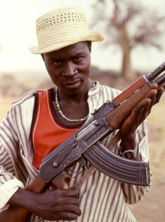 Las montañas de Nuba, Sudán-enero 13, 2008:fighter de la tribu Nuba Sudán con su Kalashnikov.Since de 1991, los Nuba lucharon solos sin suministros, dependiendo exclusivamente de apoyo local. Miles de jóvenes Nuba han dejado para el sur, arriesgando sus vidas