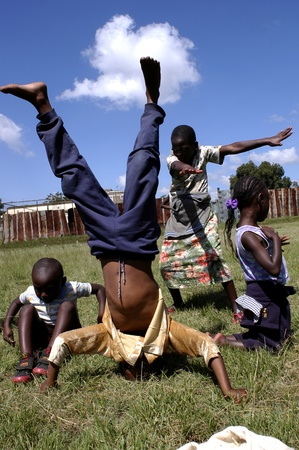 retrieves: Nairobi,Kenya January 10,2009.Street children play happily in a park.There are many street children in Nairobi.The association Resque Dada was born in Nairobi retrieves them through the streets of the capital to give it a decent life Editorial