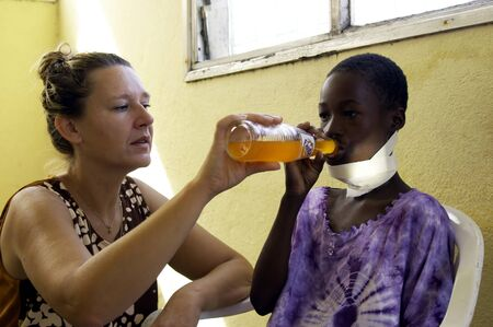ni�os enfermos: Beira, Mozambique-el 10 de enero, 2010:Swiss mujer, Barbara Hofmann, ayuda a un ni�o que se hizo.Desde 1989, despu�s de ver la realidad de la guerra, ha abierto un centro en su estructura y recoge ni�os v�ctimas de guerra, hu�rfanos y abandonados d�ndoles la educaci�n
