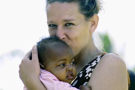 africa kiss: Beira,Mozambique-January 10,2010:Swiss woman,Barbara Hofmann,with a small child.Since 1989 after seeing the reality of war,it collects in its structure in Beira,children affected by war,orphaned and abandoned
