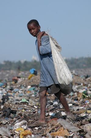 hambriento: Maputo, Mozambique - 14 de mayo de 2004: un ni�o pobre en la capital de vertedero de Maputo en Mozambique. Hay muchos ni�os de la calle en la basura en busca de alimentos, botellas, hierro Latina revender
