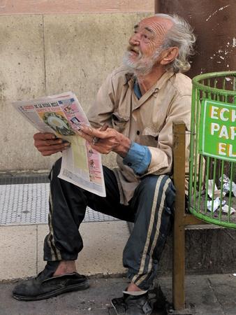 cigar smoking man:   Habana, Cuba-febrero 20,2009: un pobre hombre solo en las calles de la Habana. Hay muchas personas que piden limosna en la capital cubana                               Editorial