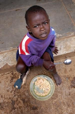 Nairobi, Kenia, el 17 de enero de 2004. niño come en las calles de Nairobi.There es muchos los niños abandonados en las calles sólo