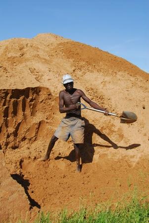 Shinyanga, Tanzania, 18 de marzo de 2010: Miner nieve de arena en una mina de oro. Tanzania es el tercer productor de oro en África después de Ghana y Sudáfrica.