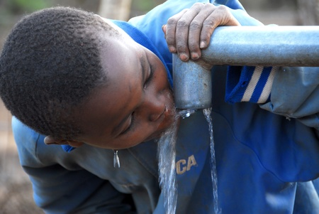 TAPS: Mtito Andes, Kenya 13 JULY 2009:child drinking water from a source,thanks to various humanitarian organizations, the people of the village of Andes Mtito can fetch water from a source. Editorial