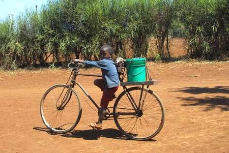 Mtito Andes,Kenya 13 JULY 2009:child carries the water with your bike thanks to various humanitarian organizations,the people of the village of Andes Mtito can fetch water from a source