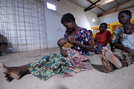 borstvoeding: Lilongwe, Malawi 10 januari: een jonge moeder gezeten op de grond nursing van haar kind.In Afrika is het normaal om te zien een borstvoeding moeder haar kind. Malawi is een van de armste landen in de wereld