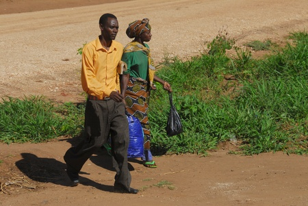 Tanzania, February 2010: African couple walking down a dirt road Stock Photo - 9083860