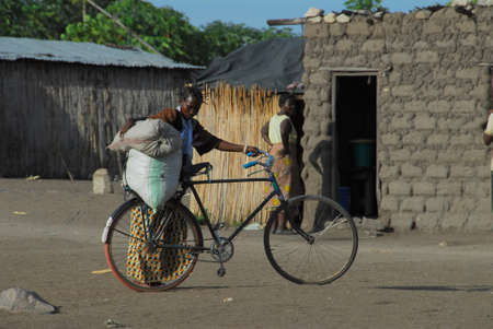 Mwanza, Tanzania February  2010: African woman loads a sack of rice on your bicycle Stock Photo - 9083855
