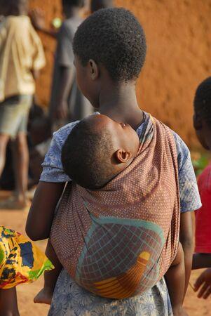 Dar Es Salam, Tanzania-15 de marzo, 2010: una niña carga un le hermanito sobre sus hombros. hermanos mayores son responsables de sus hermanos menores Editorial