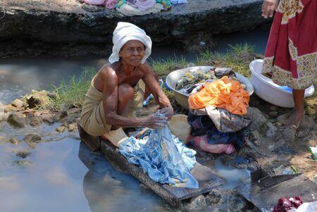 lavando ropa: Nosy Be, Madagascar-16 de octubre de 2006: una anciana lavar la ropa en un r�o. Muchas �reas ser Nosy sufren de sequ�a prolongada e intensa.