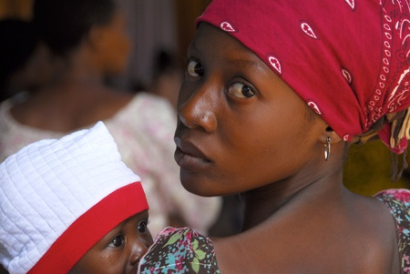 Mwanza, Tanzania - 21February, 2010: primer plano de una joven madre con su bebé en la Iglesia Evangelista