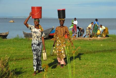 Mwanza, Tanzania y 7 de junio, 2010:Women en la orilla del lago Victoria. Las mujeres lavan su ropa en el lago y cargar los contenedores en sus cabezas
