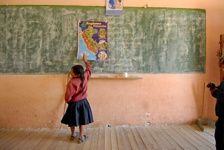 Lima, Perú â? 21 de agosto de 2007: una colegiala peruana de escrituras elementales en una gran pizarra en el aula de una escuela en Lima