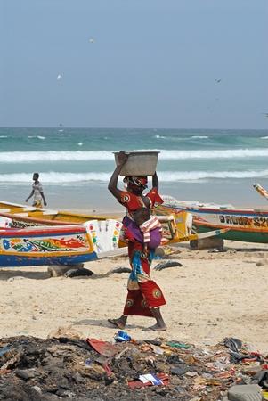 Dakar, Senegal - 8 de febrero de 2011: Senegal mujer con su beb� sobre su espalda est� caminando en la playa con los t�picos barcos de colores de los pescadores en Dakar