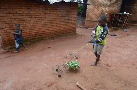 malawi: salima, malawi, 7 april 2011: an african child plays with a truck built by him with iron wire with her toy of salima in april  2011.african children's toy are built with any materials Editorial