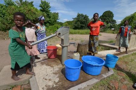 Salima, Malawi ? 10 de abril de 2011: los niños africanos toman agua de un pozo en Salima el 10 de abril de 2011. Malawi últimamente sufre de sequía frecuente y masiva.
