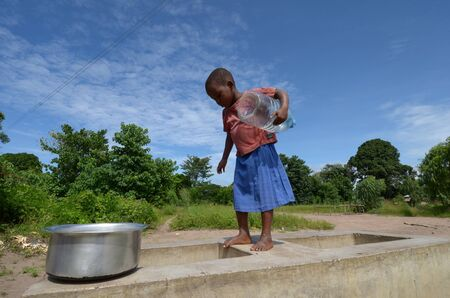 Salima,Malawi – 10 April 2011: Little girl at the edge of a well looking for water on April 10. 2011. Malawi is recently facing severe famine due to floods and drought.  Redactioneel