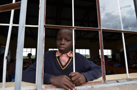 Masai Mara,Kenya,Africa,October 17, 2011. An African unidentified kid looking at the camera while studying in a small school in Masai Mara, in Masai Mara, Kenya  Stock Photo - 11117412