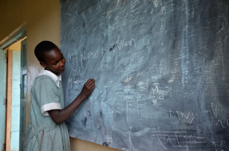 Masai Mara,Kenya,Africa; October 17.2011 : unidentified student writes his name on the blackboard at school in Masai Mara  Editorial