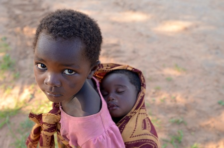 LUSAKA,ZAMBIA – DECEMBER 3,2011: unidentified child with her brother on his shoulders. Many children in Lusaka are out of school to care for siblings when parents work in the fields,  on December 3,2011 in Lusaka,Zambia