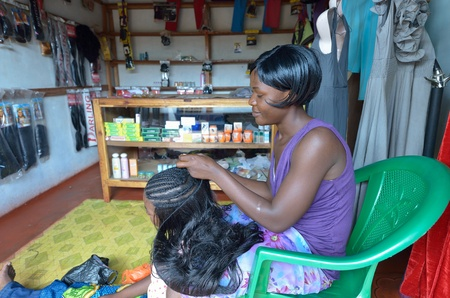 SERENJE,ZAMBIA-DECEMBER 7,2011: Hair stylist plating hairs in the city market the hairdresser