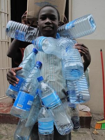 mwanza: Mwanza,Tanzania,March,14,2010 : unidentified street child collects plastic bottles to sell them in Mwanza Tanzania March 14, 2010 Editorial