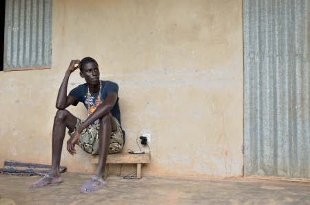 Kartiak,Senegal-September 18,2011:adolescent African and not identified sat in the terrace, of his humble house, September 18 th 2012 in Kartiak, Senegal. The region of Casamance, south of Senegal is a very poor area according to International statistic