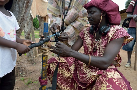 occurs: Kartiak,Senegal-September 18,2012 :An unidentified African man prepares a gun for the Boukoutt of Initiation ceremony on September 18, 2012 in Kartiak, Senegal. The ceremony occurs every 30 years and celebrates boys becoming men. Editorial