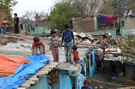 parable: New Delhi,India-February 4, 2013:children not unidentified play on the rooftops of the largest slum in New Delhi.50% of the population of New Delhi is thought to live in slums,on February 4,2013 in New Delhi