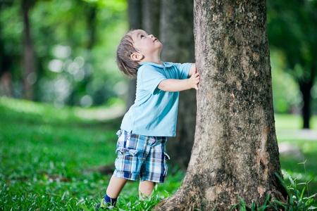Jongen spelen bij boom