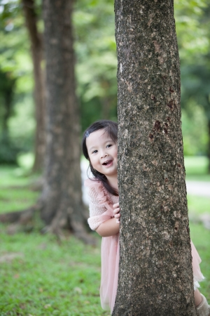kids dress: Little girl playing behind the tree