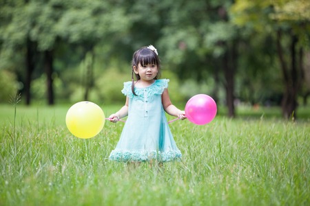 Asian little girl playing balloon in the garden photo