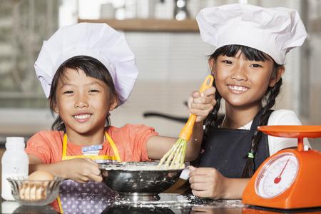 viscosity: Little asian girls stiring wheat flour and egg