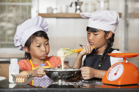stiring: Little asian girls stiring wheat flour and egg
