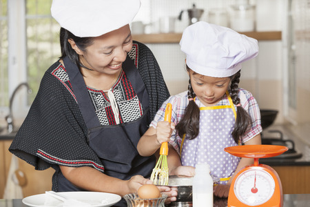 viscosity: Mother and daughter using whisk to mix egg and wheat flour Stock Photo