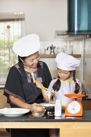 wheat flour: Mother and daughter using whisk to mix egg and wheat flour Foto de archivo