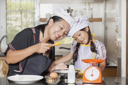 Mother and daughter using whisk to mix egg and wheat flour Stock Photo